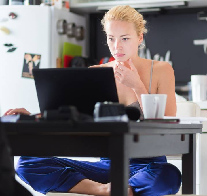 Young lady working remotely from her home kitchen