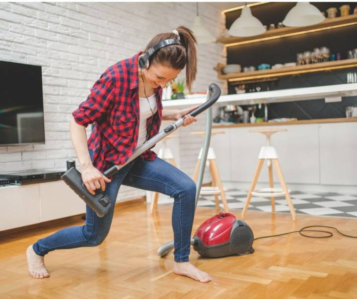 Young woman playing with vacuum cleaner