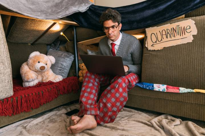 A man sitting on a sofa shelter with the laptop